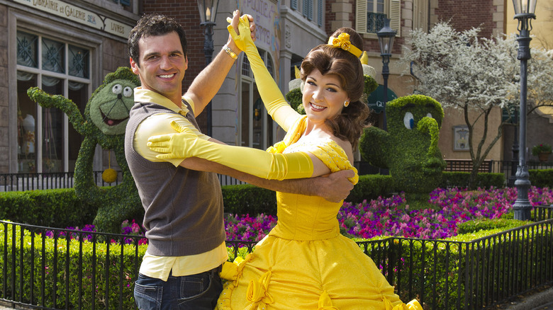 Princess Belle from Beauty and the Beast dances with a guest in Disney World
