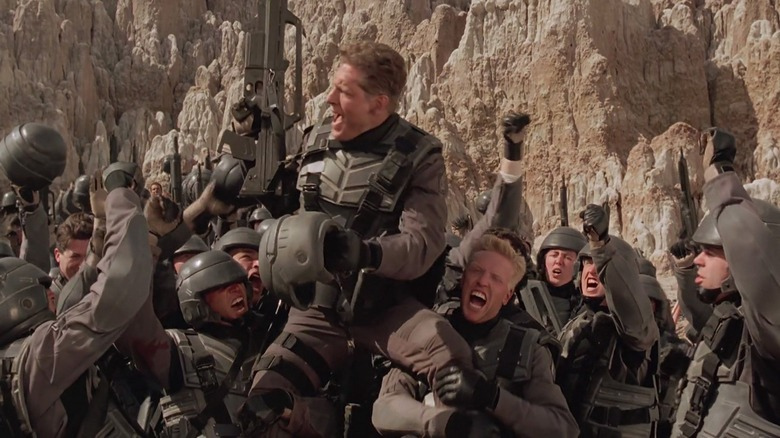 Clancy Brown surrounded by soldiers